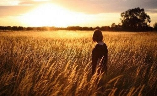 Kvinde ser solnedgangen på en mark og tænker over sammenhængen mellem selvopfattelse og depression