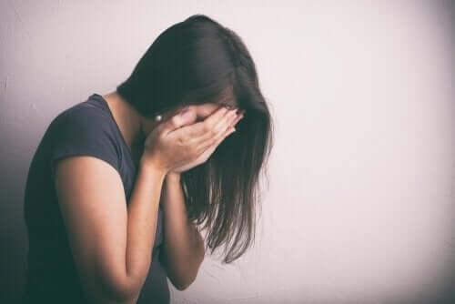 kvinde med ansigtet begravet i sine hænder