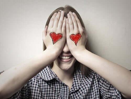 Smilende kvinde med hænder for øjnene, hvor der er tegnet hjerter på
