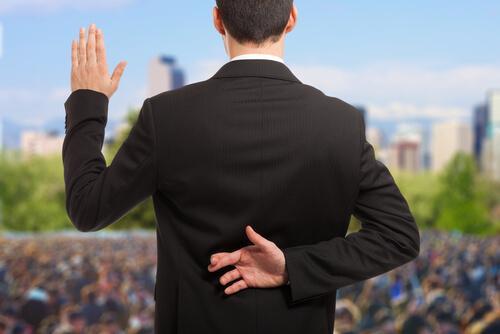 mand, der krydser sine fingre bag ryggen, mens han lover noget foran en folkemængde