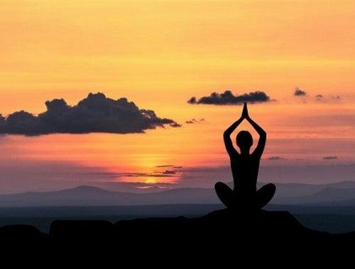 Person mediterer på bjergtop for at reducere forventningsangst