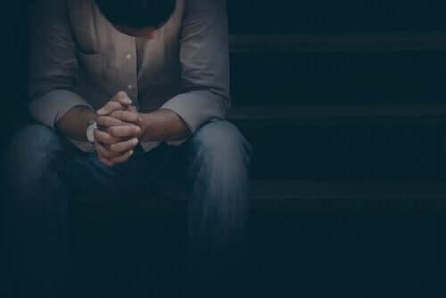 person i mørke med foldede hænder