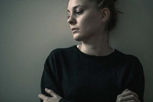 Trist kvinde foran grå væg