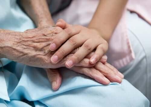 Barn holder om ældre persons hånd