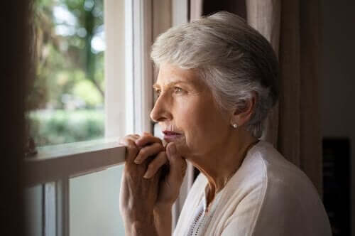 Ældre kvinde ser ud af vindue