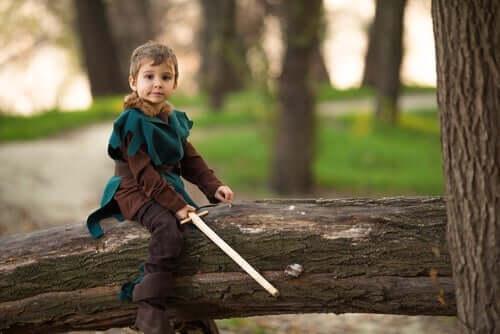 dreng, der sidder på træ, klædt ud som Robin Hood