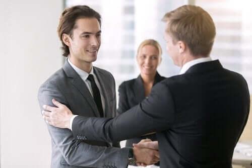 Forretningsmænd giver hinanden hånden som illustration af at være glad på andres vegne