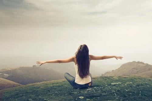Fri kvinde ved bjerglandskab symboliserer, hvordan man bliver fri ved ikke at holde fast i ting for fortiden