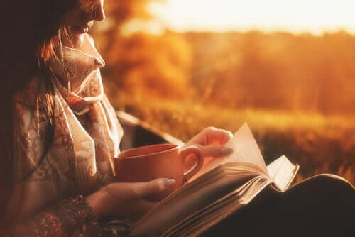 kvinde, der læser udenfor med en kop te