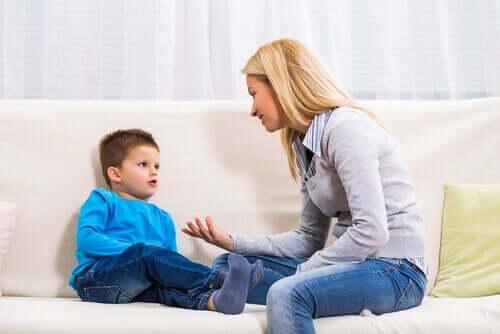 Kvinde snakker med dreng i sofa