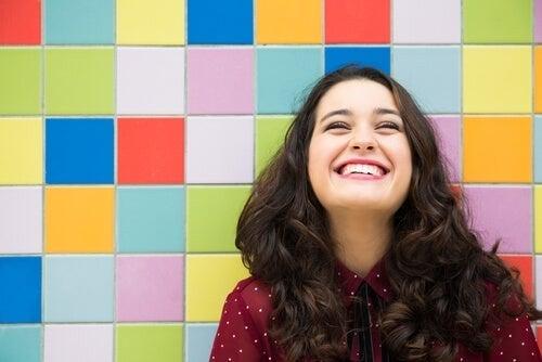 Kvinde smiler foran en farverig baggrund