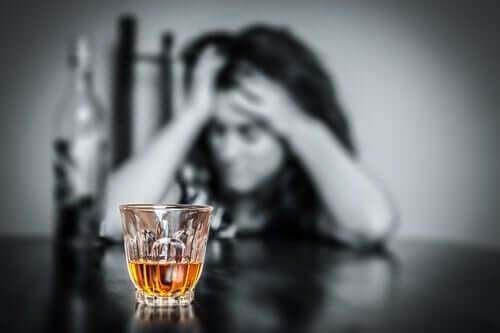 Kvinde bag glas med alkohol