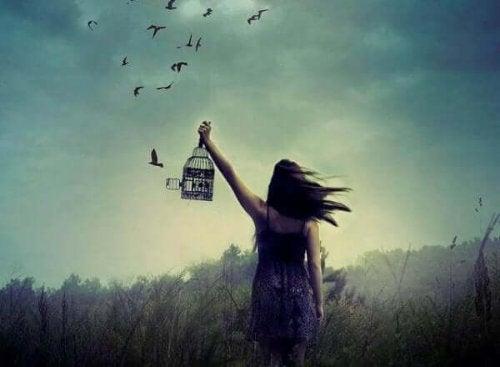 Kvinde sætter fugle fri i stedet for at holde fast i ting, hun ikke er herre over