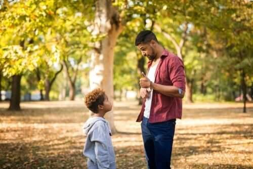 Far snakker med dreng i skov