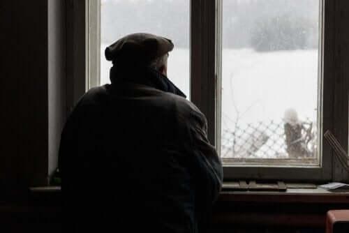 Ældre mand, der sr ud af vindue