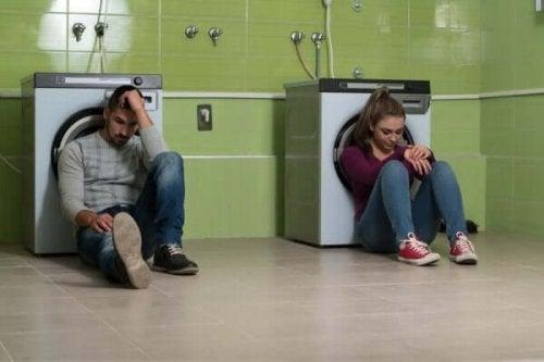 Par sidder frustreret foran vaskemaskiner som illustration af Houdini syndromet