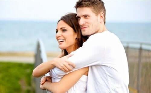 Par krammer hinanden foran hav