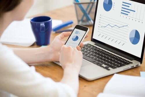 Kvinde ved computer og telefon ser på diagrammer