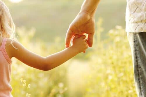 Pige holder i fars hånd