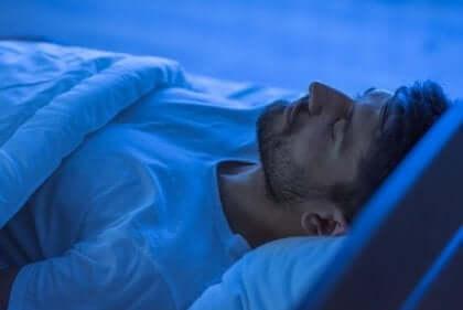 en mand sover i sin seng