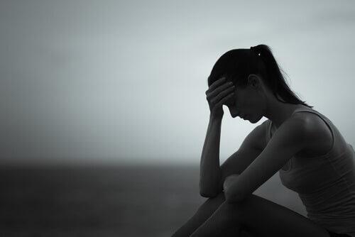 Kvinde sidder alene og er trist