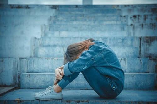 trist teenager hviler hoved på knæ