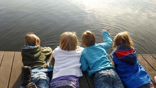 Børn ligger på bro og kigger på vand
