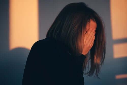 Kvinde, der skjuler ansigt bag hænder, føler skyld