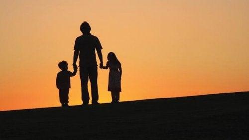 Silhuet af forælder, der holder to børn i hænderne
