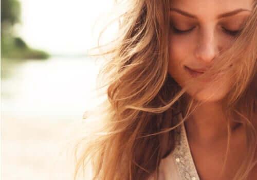 Smilende kvinde med vind i håret er tilfreds med livet