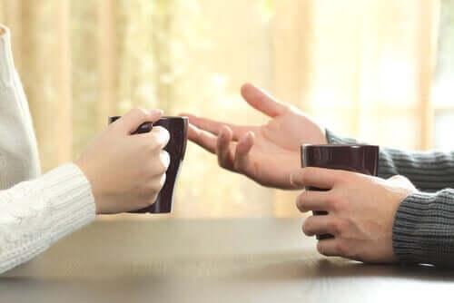 Personer taler sammen, hvilket kan ses på hænder, der holder om kaffekopper overfor hinanden