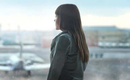 En kvinde, der kigger ud af vinduet i en lufthavn