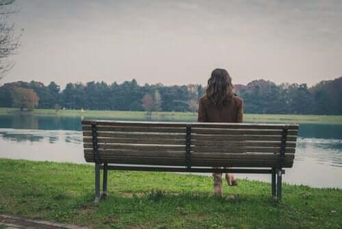 Kvinde sidder alene på bænk og ser på sø