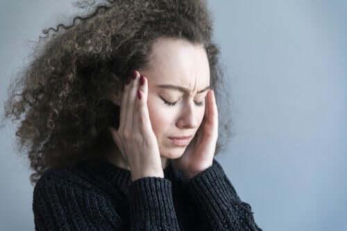 Kvinde, der tager sig til hoved, har brug for behandling af migræne