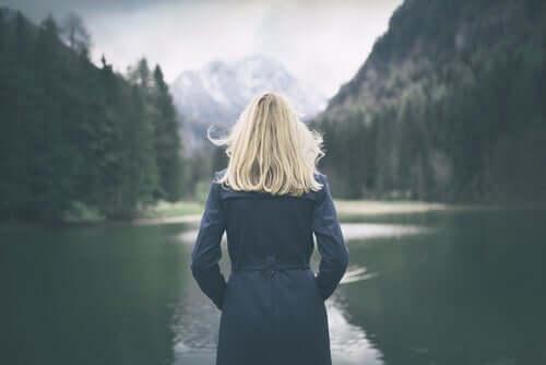 Kvinde ser på sø i skov og opfylder sit behov for alenetid
