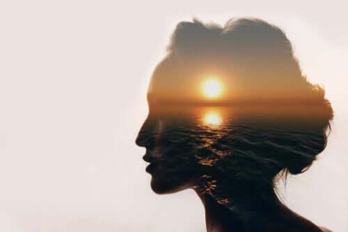 En kvinde, der tænker på samspillet mellem krop, sind og meditation, ses med solnedgang over havet