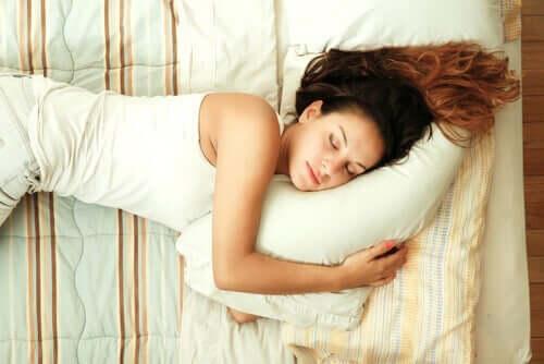 En kvinde, der sover på en seng
