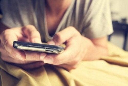 Mand sender beskeder fra sin mobiltelefon