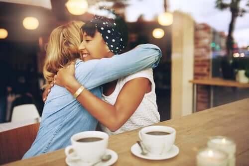 Kvinder krammer på café