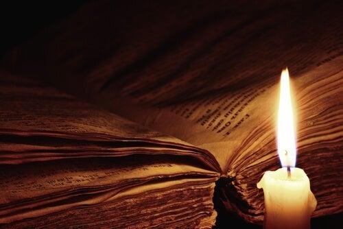 Gammel bog oplyst af stearinlys