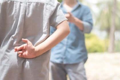 dreng, der krydser fingre bag ryggen