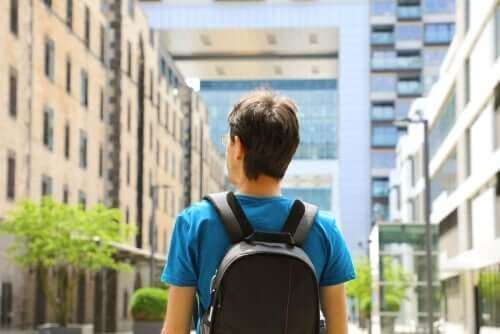 Mand med rygsæk foran høje bygninger