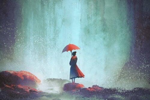 Kvinde med paraply ved vandfald arbejder på at tage afstand fra oplevelser