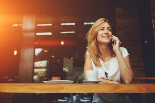 kvinde, der smiler, mens hun taler i mobil