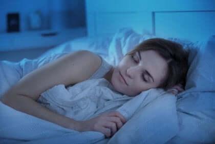 kvinde, der sover, og anerkender vigtigheden af hvile og søvn