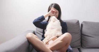 Kvinde med hund i sofa sidder og græder