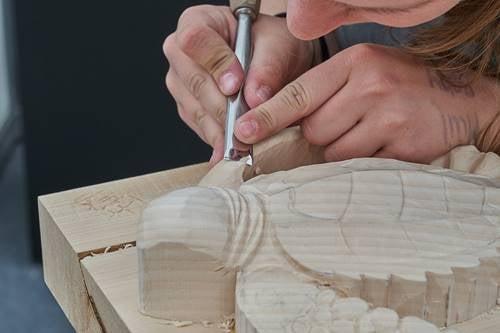 Person laver skildpadde af træ