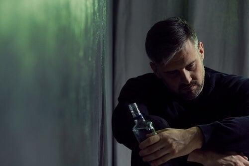 Mand ser nedtrykt ud, mens han sidder med en flaske alkohol