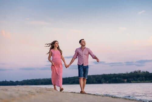 Ungt par går hånd i hånd på strand