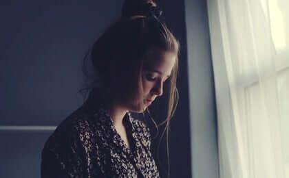 Trist pige ved vindue